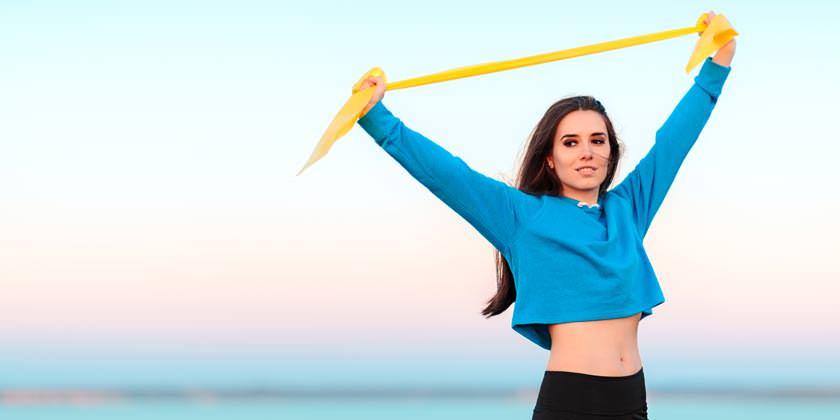 Una chica trabaja musculación con banda elástica en la playa